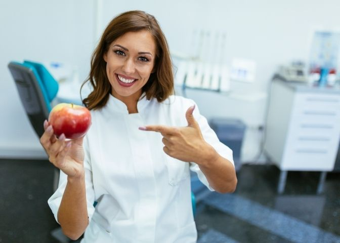 Female dentist pointing to an apple